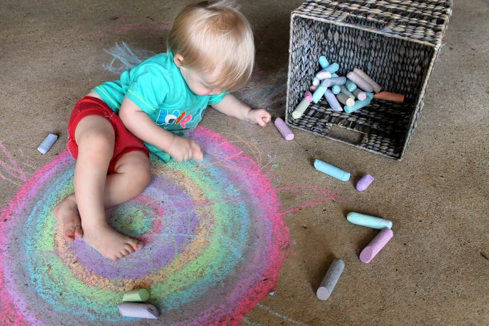 In ECE children learn in different ways - child playing with color chalk