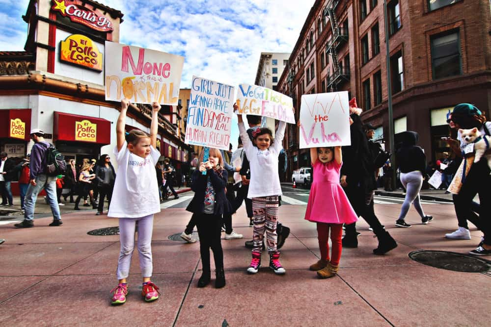ECE program teaches children early the importance members of society - four girls holding up signs