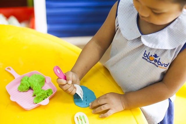 Play time is important in Preschool and ECE education - image of young girl cooking with clay